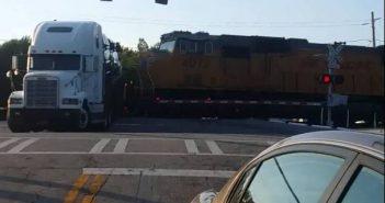 Autotreiler jääb raudteeülesõidukohal kinni ja jääb rongile ette
